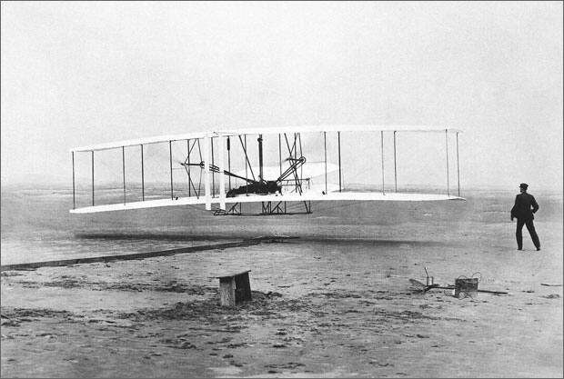Orville Wright is at the controls of the Flyer as his brother Wilbur, stands nearby during the plane's first flight at Kitty Hawk, N.C., December 17, 1903. (AP Photo/John T. Daniels)
