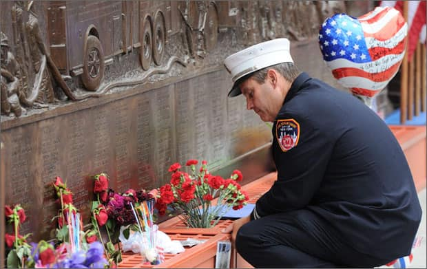 A New York city firefighter pauses at the firefighters memorial wall that displays the names of victims of Sept. 11  (AP Photo/The Canadian Press, Sean Kilpatrick)