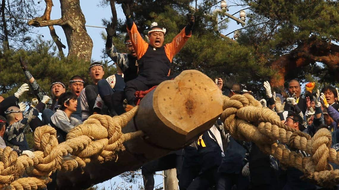 Men ride on a giant log down a hill