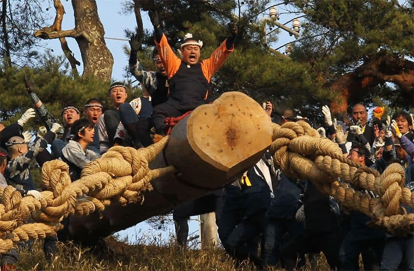Men ride on a giant log down a hill.