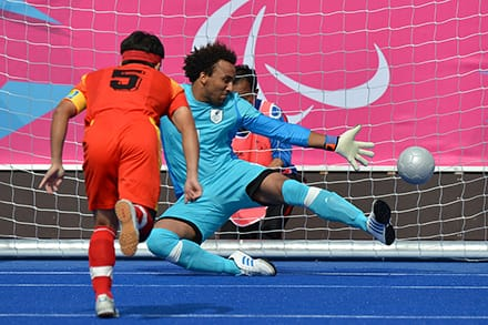 a player kicks the ball towards the net as the goalkeeper stretches out his arm and leg to block it