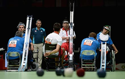 three boccia players use ramps to help them roll the balls on to the court