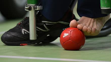 a close-up of a player's bare foot holding on to soft red boccia ball