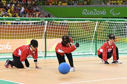 a goalball player in front of the net rolls the ball towards the other team