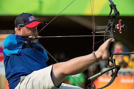 an athlete uses his foot to hold the bow and pulls the bow back using an assistive device