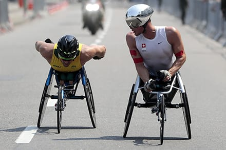 two athletes compete in the marathon in special tricycles