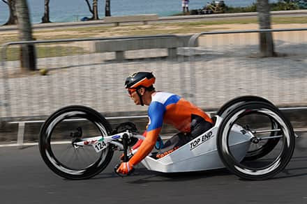an athlete uses his hands to power his handcycle on an outside track