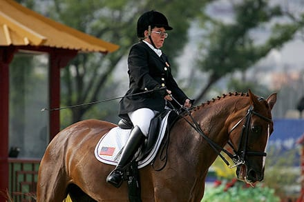 a rider holds short whip in their right hand as they sit astride their horse