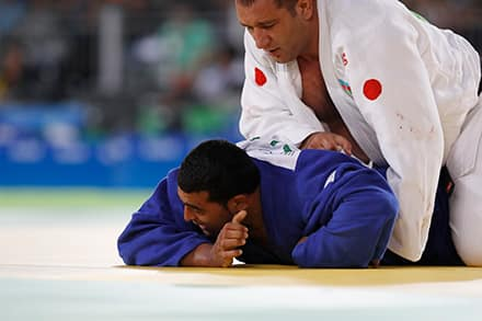 an athlete with a white outfit and red dots is holding another one down on the mat