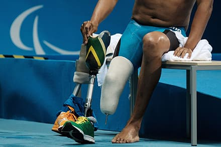 a swimmer takes off their prosthetic leg