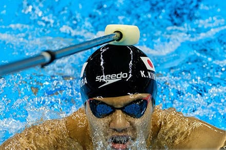 a blind swimmer is tapped on the hear with a pole