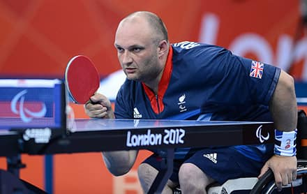 an athlete sits in a wheelchair with a cushion in the seat and is ready to hit the ball