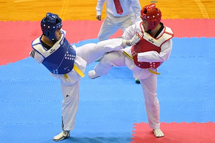 one athlete kicks the other in the chest which is protected with a vest