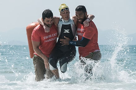 an athlete has her arms around the shoulders of the handlers as they help her out of the water