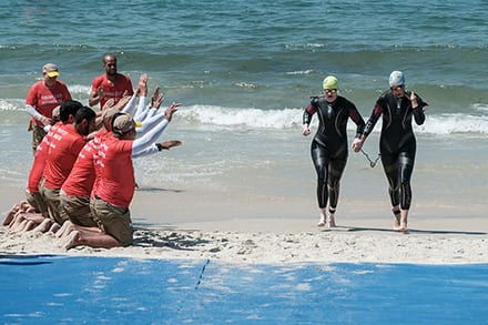 an athlete holds the hand of their guide as they both come up the shore from the water and guides cheer them on