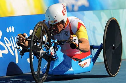 an athlete sits in his handcycle and uses his hands to pedal the front wheel