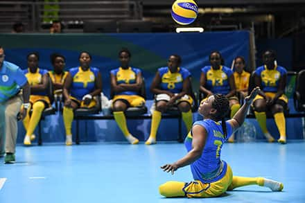 a paralympic athlete sits on the volleyball court floor to serve the ball