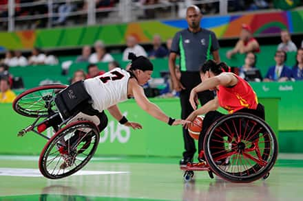 a female athlete tilts her wheelchair onto one wheel to try and read for the ball in the lap of another athlete