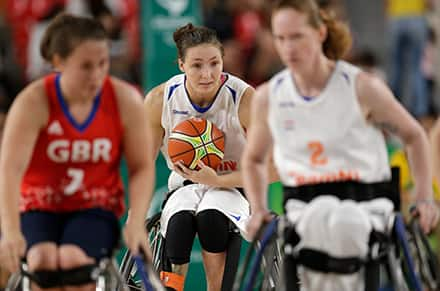 a female athlete holds the basketball in her lap as she pushes her wheelchair forward on the court
