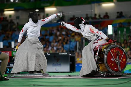 two athletes in wheelchairs with aprons on their laps that cover their legs as well