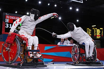 Two athletes in their wheelchairs with their swords out and you can see the metal frames on the ground
