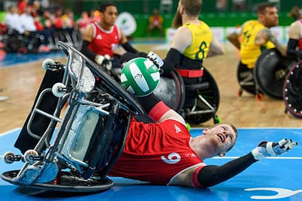 an athlete's wheelchair is on its side as he hold the ball