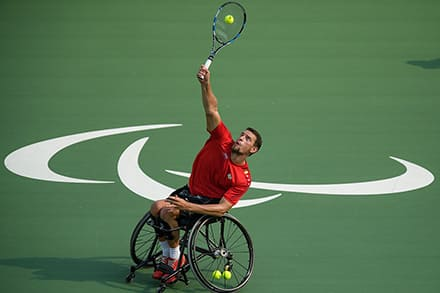 an athlete reaches up overhead to hit the ball with his tennis racket