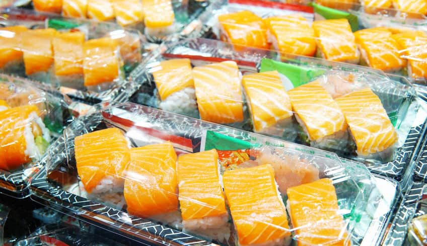 Sushi packaged up in plastic take-out containers.