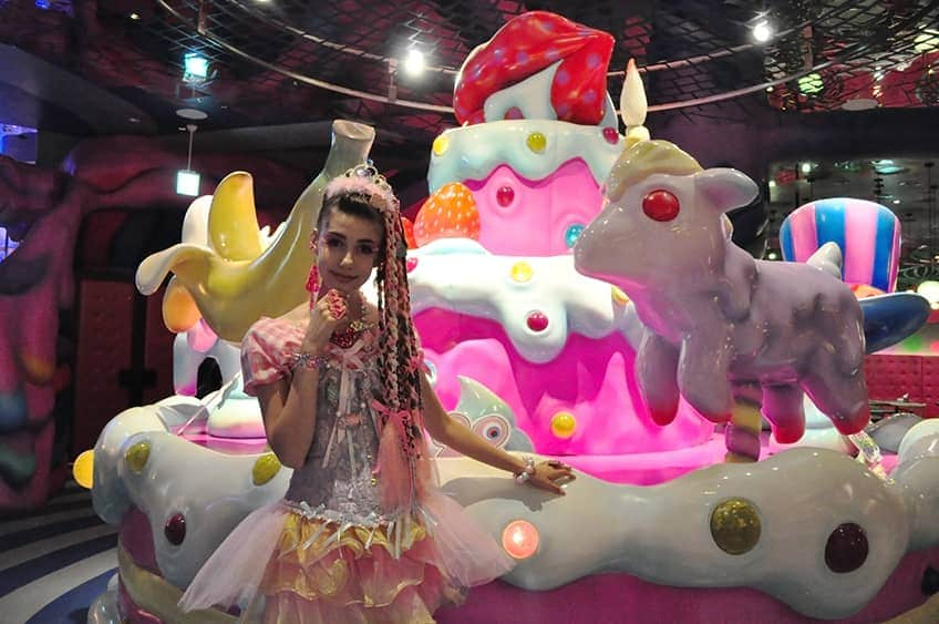 a girl in a colourful costume stands in front of a gigantic plastic cake
