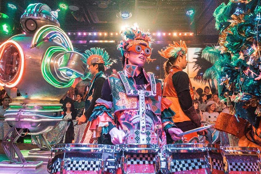 people in costume play the drums while surrounded by giant robots