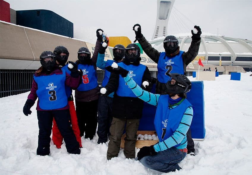 A group dressed for winter poses in the snow. They all are holding snowballs.