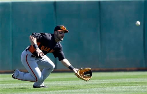 San Francisco Giants center fielder Andres Torres makes a diving attempt at a fly ball from Los Angeles Dodgers' Skip Schumaker during the second inning of an exhibition spring training baseball game on Tuesday, Feb. 26, 2013 in Glendale. Ariz.  Schumaker got a double on the play. (AP Photo/Marcio Jose Sanchez)