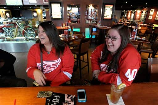 Detroit  Red Wings fans Katie Miller, left, of Toledo, Ohio, and Emily Radwanski, of Roseville, Mich., wear their Red Wings jerseys while hanging out at the Hockeytown Cafe in Detroit, Sunday, Jan. 6, 2013. With the season on the line, the NHL and the players' association agreed on a tentative pact to end a 113-day lockout and save what was left of a fractured hockey schedule. (AP Photo/The Detroit News, David Guralnick)