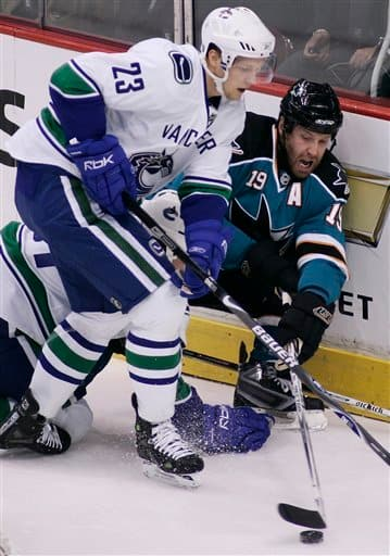 File-This Oct. 15, 2007 file photo shows San Jose Sharks' Joe Thornton (19) trying to play the puck while getting checked into the end boards by Vancouver Canucks' Alex Edler (23), of Sweden, during the first period of NHL hockey action in Vancouver.  The  Canucks re-signed Edler to a six-year deal on Friday Jan. 18, 2013. The 26-year-old had 11 goals and 38 assists in 82 games with the Canucks last season. (AP Photo/Richard Lam, The Canadian Press,File)