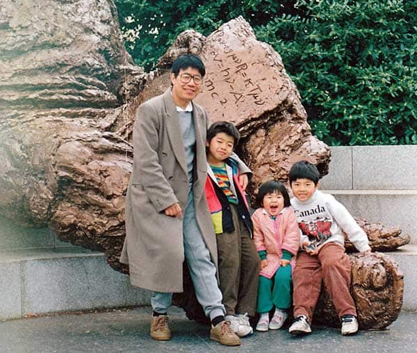 Man with this 3 children in front of a rock