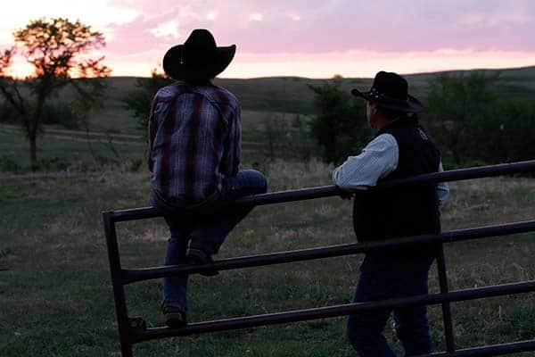 cowboy sitting on fence