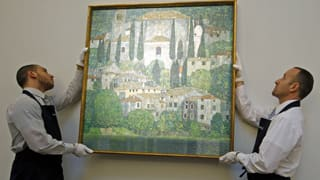 Workers hang Kirche in Cassone (Church in Cassone) by Gustav Klimt at Sotheby's auction house in London on Jan. 12.