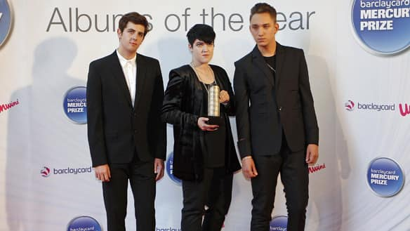 Members of British band The XX are, from left, Jamie Smith, Romy Madley Croft and Oliver Sim. They hold their nominee trophy as they arrive for the Mercury Prize awards in London on Tuesday. They won.