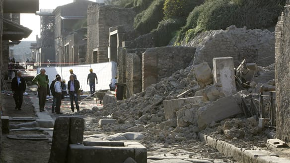 People stand near debris after a house once used by gladiators to train before combat collapsed in Pompeii on Nov. 6, 2010. Pompeii is the ancient Roman city next to Naples that was destroyed in AD 79 by the eruption of the Mount Vesuvius volcano. Q host <b> Jian Ghomeshi</b> speaks to journalist Amanda Ruggeri about why Italians are worried about their archeological heritage. (Ciro De Luca/Reuters)