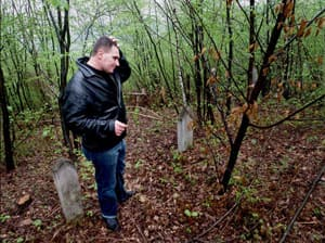 A man stands in a forest where people were buried beneath existing graves to hide the bodies from investigators.
