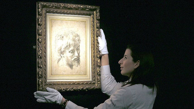 A Sotheby's employee adjusts Head of a Young Apostle, a black chalk drawing by Renaissance master Raphael, which has sold for $47 million in London.