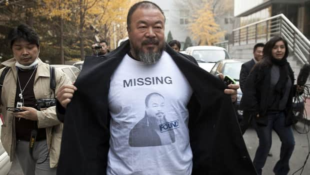 Chinese dissident artist Ai Weiwei reveals a shirt bearing his portrait as he walks into the Beijing Local Taxation Bureau on Nov. 16, to deal with his conviction for what Chinese authorities say were