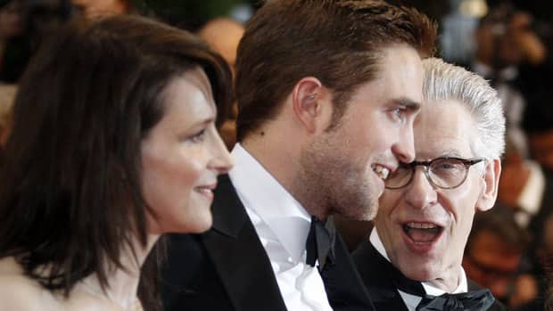 Cosmopolis cast members Juliette Binoche, left, and Robert Pattinson, centre, pose on the red carpet with director David Cronenberg on Friday.
