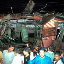 People stand outside a train coach that was destroyed in a bomb blast in Mumbai.