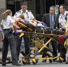 A woman is taken from the shooting scene to a waiting ambulance.