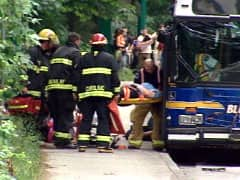 Firefighters take injured passengers off the transit bus on Friday in Vancouver.