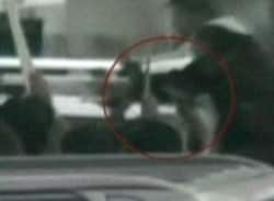 Video footage of Benazir Bhutto's last moments shows a man in a crowd aiming a gun (circled) at the Pakistani opposition leader. A suicide bomb went off seconds later.