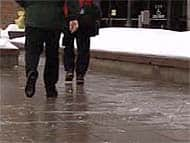 Pedestrians in Ottawa negotiate a shiny, slippery coating of ice left on a sidewalk by freezing rain Monday morning.