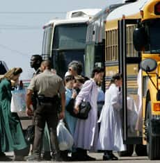 Police escort members of the Fundamentalist Church of Jesus Christ of Latter Day Saints on to a school bus in Eldorado, Texas, on Sunday.