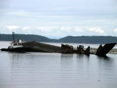 A tugboat was used to move a barge that overturned in Johnstone Strait last August.